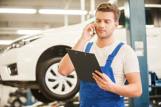 Omówienie niektórych problemów z samochodem. przystojny młody mężczyzna rozmawiający przez telefon komórkowy i patrzący na schowek stojąc w warsztacie z samochodem w tle