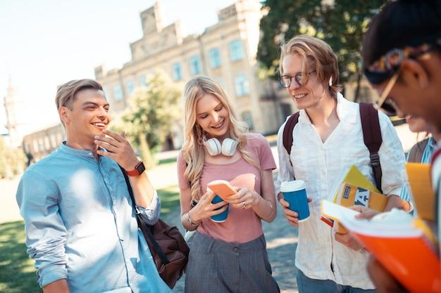 Omówienie przyszłych zajęć. wesoły koledzy z grupy stojący razem na dziedzińcu uniwersyteckim, pijący kawę i rozmawiający.