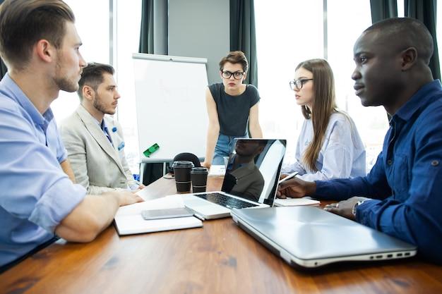 Omówienie udanego projektu. grupa młodych ludzi biznesu wesoły pracy i komunikacji siedząc przy biurku wraz z kolegami siedzącymi w tle.