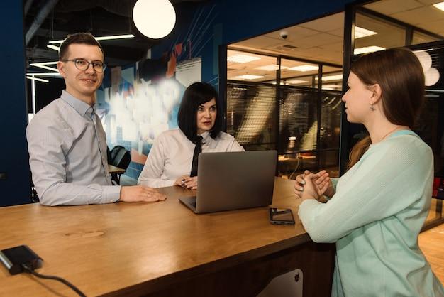 Omówienie z klientem młodego biznesmena i pracowników firmy w nowoczesnym biurze