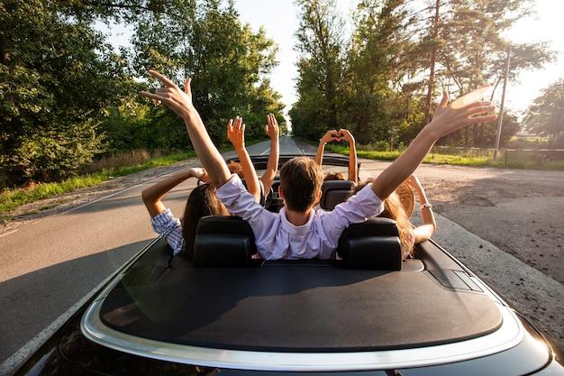 Ompany młodych ludzi jeżdżących kabrioletem na drodze i trzymających ręce w górę w ciepły słoneczny dzień. widok z tyłu. .