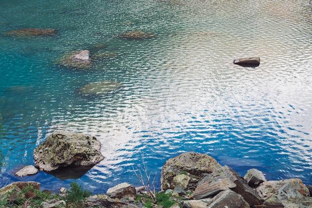 Omszałych kamieni w błyszczącym górskim jeziorze. czyści błękitną wodę powierzchnię w średniogórzach w słonecznym dniu z kopii przestrzenią. skalisty skalisty brzeg jeziora z roślinami. światło słoneczne.