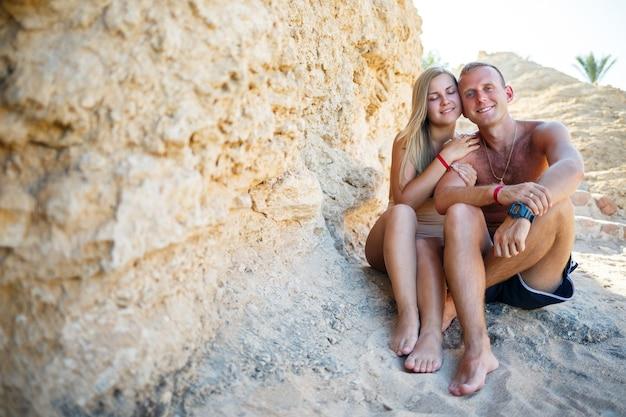 On i ona są na piasku plaży, słońce. para siedząca nad brzegiem morza, miłość, czułość, wakacje