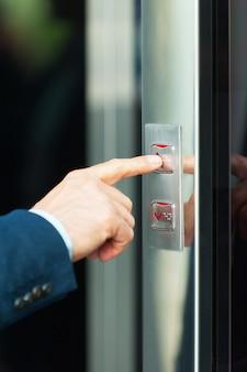 On idzie w górę. przycięty obraz męskiej ręki naciskającej przycisk windy
