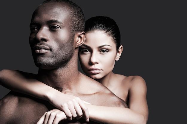 On jest moim człowiekiem. piękna kaukaska kobieta, która łączy się z przystojnym afrykaninem i patrzy w kamerę, stojąc na szarym tle