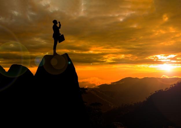 On pokazuje rękę i stoi na klifie. koncepcja osiągnięcia i sylwetka.
