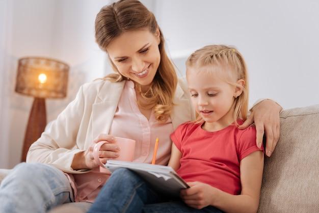 Ona jest bystra. szczęśliwa pozytywna radosna matka uśmiechając się i przytulając córkę, patrząc na jej notatki