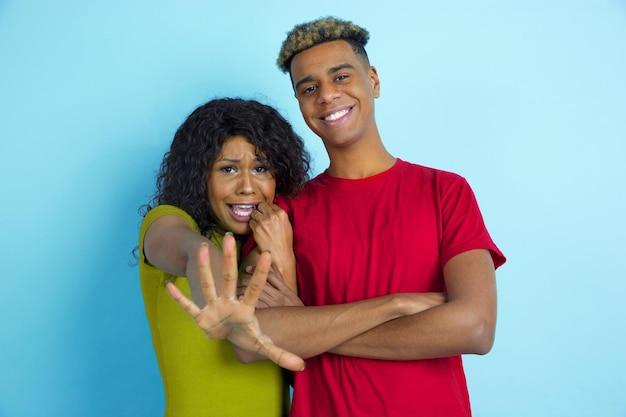 Ona się boi, on się śmieje. młody emocjonalny afroamerykanin piękny mężczyzna i kobieta w kolorowe ubrania na niebieskim tle.