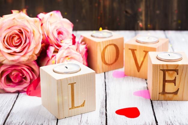 Oncept walentynki: płonące świece i słowo miłość wykonane z drewnianych świeczników