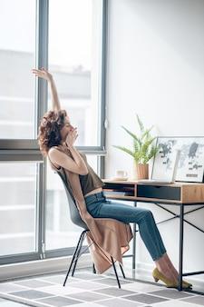 Online. ciemnowłosa kobieta siedzi z telefonem w ręce