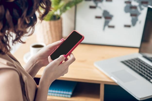 Online. młoda kobieta trzyma smartfon w dłoniach