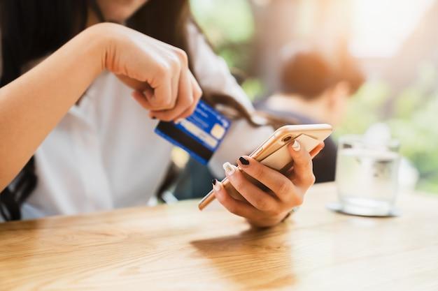 Online płatniczy lub mobilny interneta bankowości pojęcie - kobieta wręcza trzymać smartphones i cr