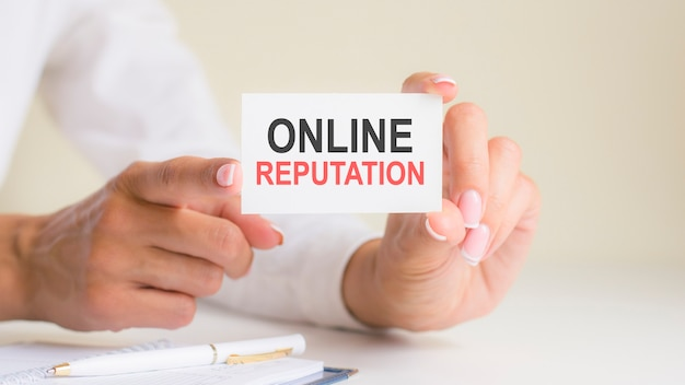Online reputacja napis na białej kartce papieru w rękach kobiety. czarne i czerwone litery na białym papierze. koncepcja biznesowa, szary backgrond