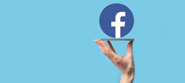 Onok, ukraina - 14 lipca 2021: biznesmen trzyma, klika, ikonę facebooka w dłoniach. sieć społecznościowa network.global i dane klienta connection.international sieć.