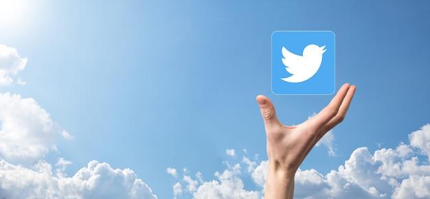 Onok, ukraina - 14 lipca 2021: biznesmen trzyma, klika, ikonę twitter w swoich rękach. sieć społecznościowa network.global i sieć connection.international klienta danych.