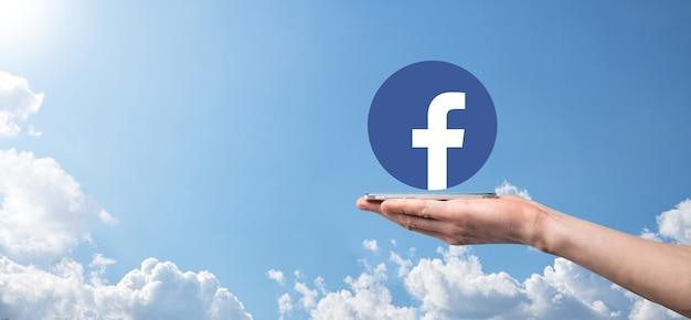 Onok, ukraina - 14 lipca 2021: biznesmen trzyma, kliknięcia, ikona facebooka w jego rękach. sieć społecznościowa network.global i sieć connection.international danych klienta.