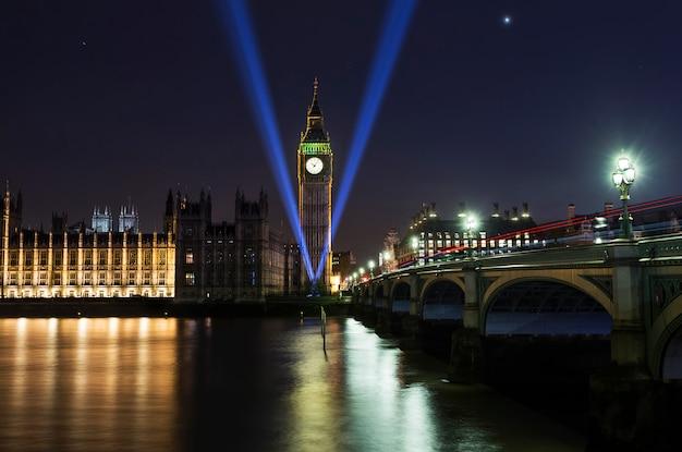 Opactwo westminsterskie i big ben nad tamizą w londynie z refleksją nad rzeką w nocy. pomnik ii wojny światowej