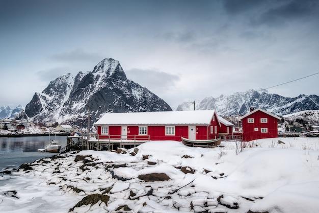 Opad śniegu na czerwień domu z schronieniem w dolinie na oceanie arktycznym