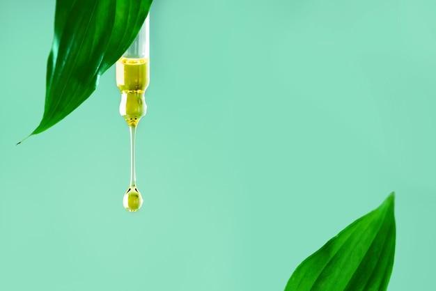Opadająca kropla klarownego naturalnego oleju, serum, kosmetyki z liściem