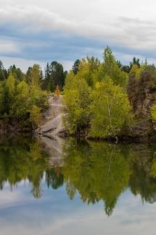 Opadające liście odbite w jeziorze z lustrzaną powierzchnią wody.