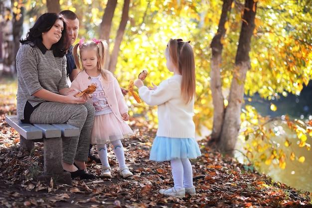 Opadanie liści w parku. dzieci na spacer po jesiennym parku. rodzina. jesień. szczęście.