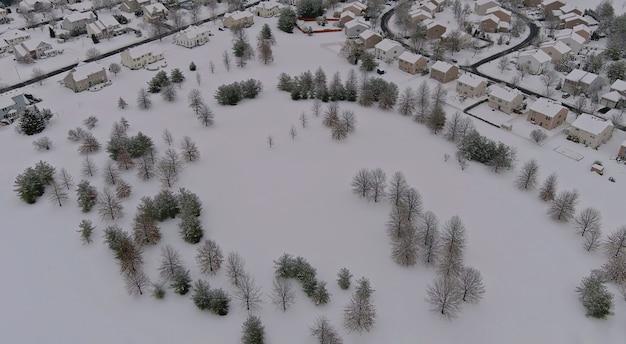 Opady śniegu nad małym miasteczkiem mieszkalnym z dachami pokrytymi śniegiem domy w usa wsi zimą