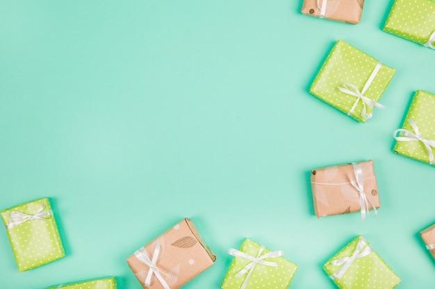Opakowane prezenty związane z białą wstążką łuk na zielonym tle