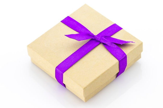 Opakowane pudełko vintage z fioletową wstążką na białym tle