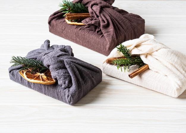 Opakowania prezentowe wielokrotnego użytku z ekologicznego materiału z brunchem z jodły, laską cynamonu i suchym plasterkiem pomarańczy. alternatywne opakowanie do pakowania prezentów świątecznych wielokrotnego użytku. koncepcja zero odpadów. skopiuj miejsce