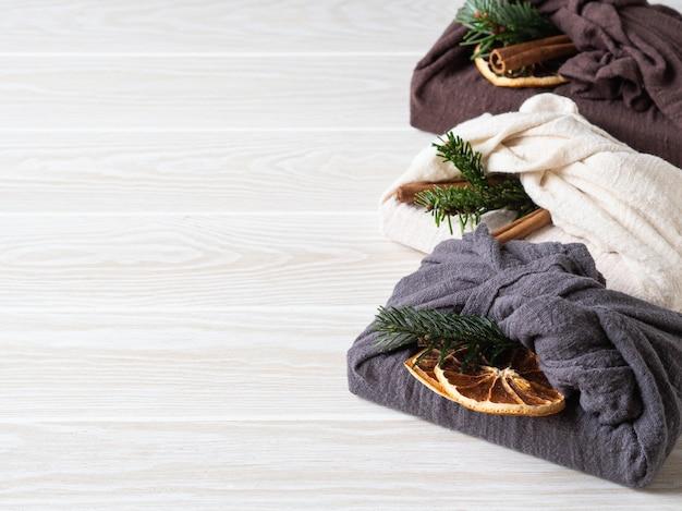 Opakowania prezentowe wielokrotnego użytku z ekologicznego materiału z brunchem z jodły, laską cynamonu i suchym plasterkiem pomarańczy. alternatywne opakowanie do pakowania prezentów świątecznych wielokrotnego użytku. koncepcja zero odpadów.
