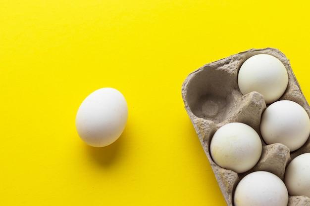 Opakowanie jaj kurzych gospodarstwa w tekturowym pojemniku na żółtym tle. zdrowe jedzenie. widok z góry na płasko, z miejsca na kopię.