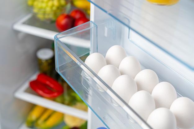 Opakowanie jaj na półce lodówki z bliska