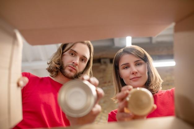 Opakowanie. młody, troskliwy długowłosy facet i dziewczyna w identycznych koszulkach wkładają konserwy do pudełek w centrum charytatywnym