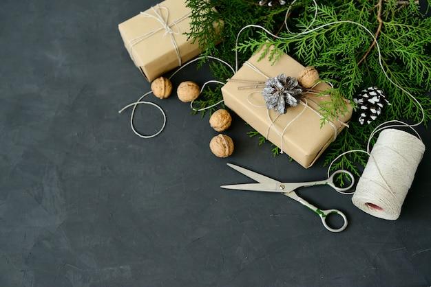 Opakowanie owijania rustykalne ekologiczne opakowania z brązowego papieru, sznurka i jodły naturalnej na ciemnym tle