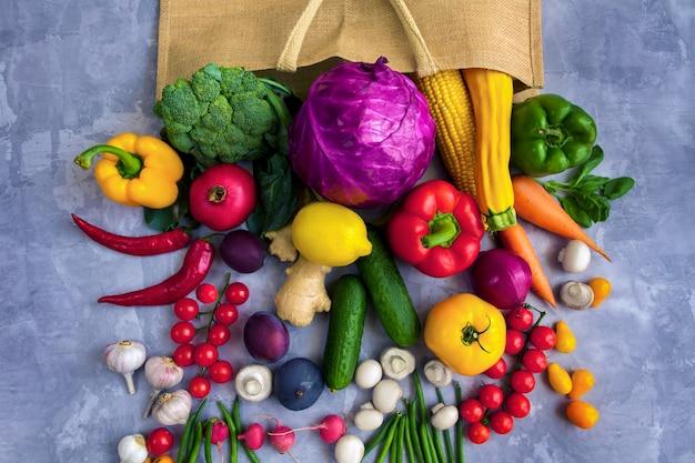 Opakowanie papierowe wegańskie wegetariańskie ze świeżymi kolorowymi smacznymi surowymi organicznymi surowymi zdrowymi warzywami i owocami: kapustą, brokułami, pieprzem, marchewką, pomidorem, pieczarkami, chili na białym tle na szarym tle