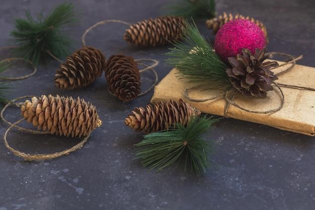 Opakowanie prezentów w papier pakowy z świątecznych dekoracji na ciemnym tle
