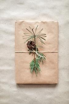 Opakowanie prezentowe na książkę lub laptopa w papier rzemieślniczy przewiązane sznurkiem i ozdobione gałązką jodły ze stożkiem
