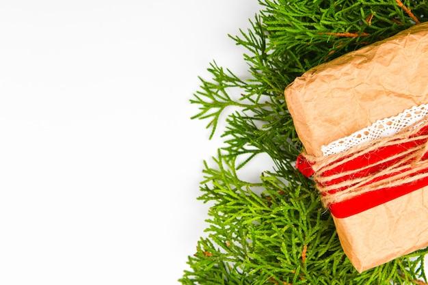 Opakowanie prezentowe wykonane z papieru na białej powierzchni. zielone gałęzie. miejsce do pisania. widok z góry. gałęzie choinkowe zi ręcznie robiony prezent z papieru pakowego kraft, na białym tle.