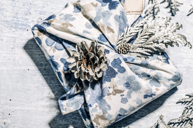 Opakowanie prezentowe zero waste w tradycyjnym japońskim stylu furoshiki. niebieskie, ręcznie robione opakowanie prezentowe na boże narodzenie z tui i rożkiem z tkaniny. ekologiczna koncepcja ekologiczny wystrój bożonarodzeniowy.