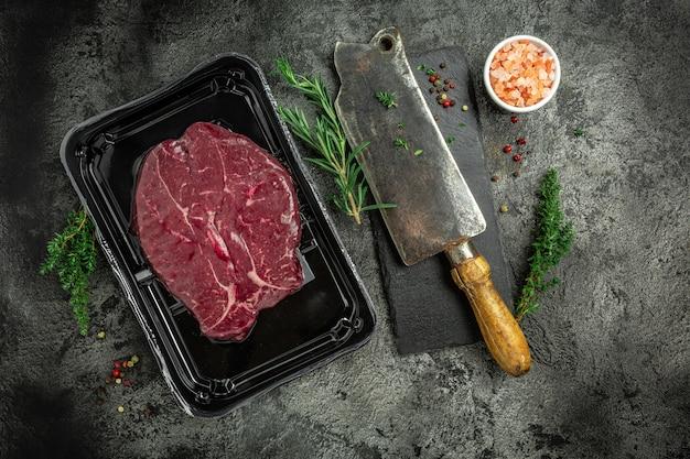 Opakowanie próżniowe 2 surowych steków wołowych z polędwicy wołowej w półfabrykacie mięsnym pakowanym na czarnym tle. widok z góry.