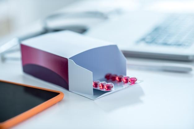 Opakowanie z czerwonymi tabletkami i urządzeniami na stole