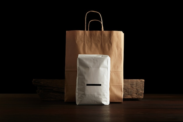 Opakowanie z produktami detalicznymi: duża hermetyczna torebka biała z pustą etykietą przed papierową torbą i rustykalną drewnianą cegłą na czerwonym stole