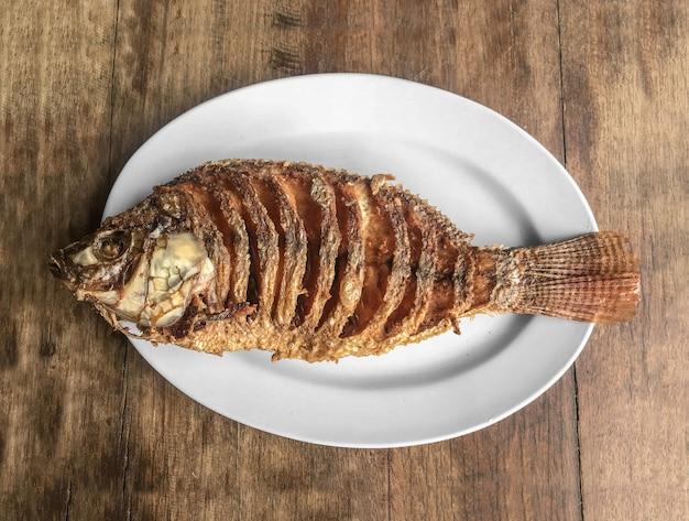 Opalane danie rybne tilapia na tle stół z drewna.