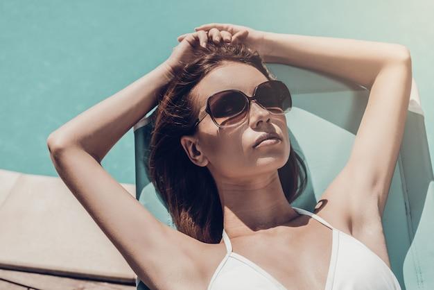 Opalanie przy basenie. widok z góry pięknej młodej kobiety w białym bikini relaksującej się na leżaku przy basenie