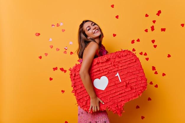 Opalona brunetka dziewczyna korzystająca z treści multimedialnych. portret uśmiechniętej damy z obsesją na punkcie sieci społecznościowych.
