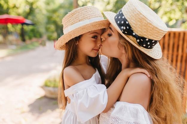 Opalona brunetka dziewczyna w słomkowym kapeluszu ozdobionym białą wstążką obejmuje mamę i odwraca wzrok. długowłosy młoda kobieta stojąca obok drewnianego płotu z miłością całuje swoją córeczkę.