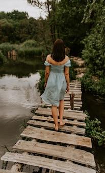 Opalona brunetka przechodzi samotnie przez rzekę starym drewnianym mostem