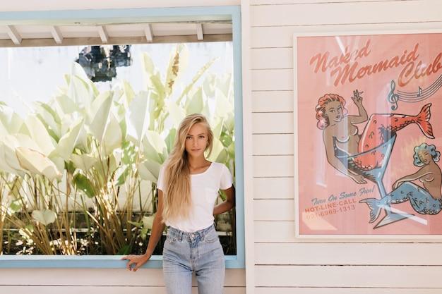 Opalona, długowłosa kobieta stojąca w pewnej pozie podczas pozowania przy oknie. zdjęcie entuzjastycznej dziewczyny w dżinsach i białej koszulce uśmiechniętej w letni dzień.