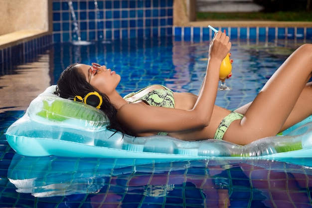 Opalona dziewczyna pozuje leżąc na przezroczystym materacu przy koktajlu