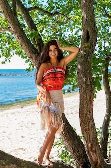 Opalona dziewczyna stoi przy drzewie na plaży